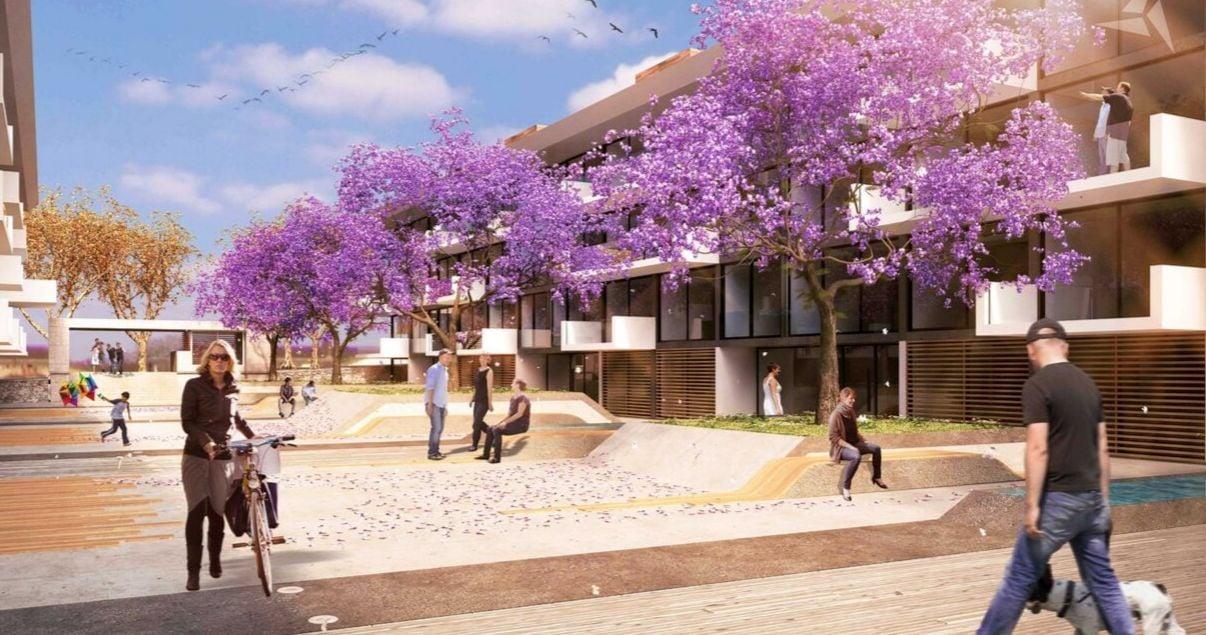 Exterior del edificio Molino del Parque con flores violetas y gente de Lamorte _ Asociados