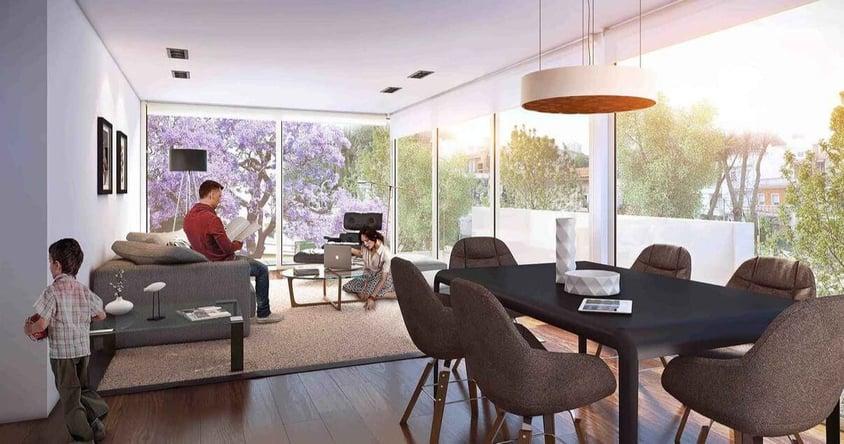 Interior de un apartamento con una familia y una mesa con sillas en el edificio Molino del Parque de Lamorte _ Asociados