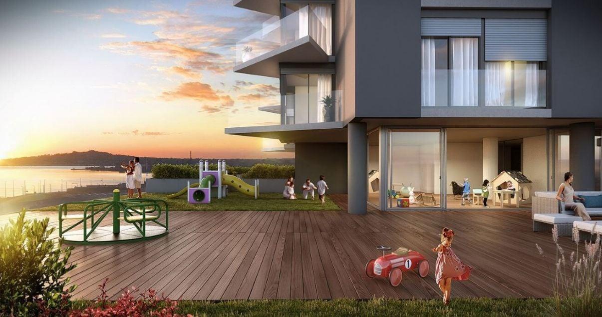 Deck y exterior del edificio Nostrum Bay en un dia soleado con juegos de niños de la desarrolladora inmobiliaria Altius Group