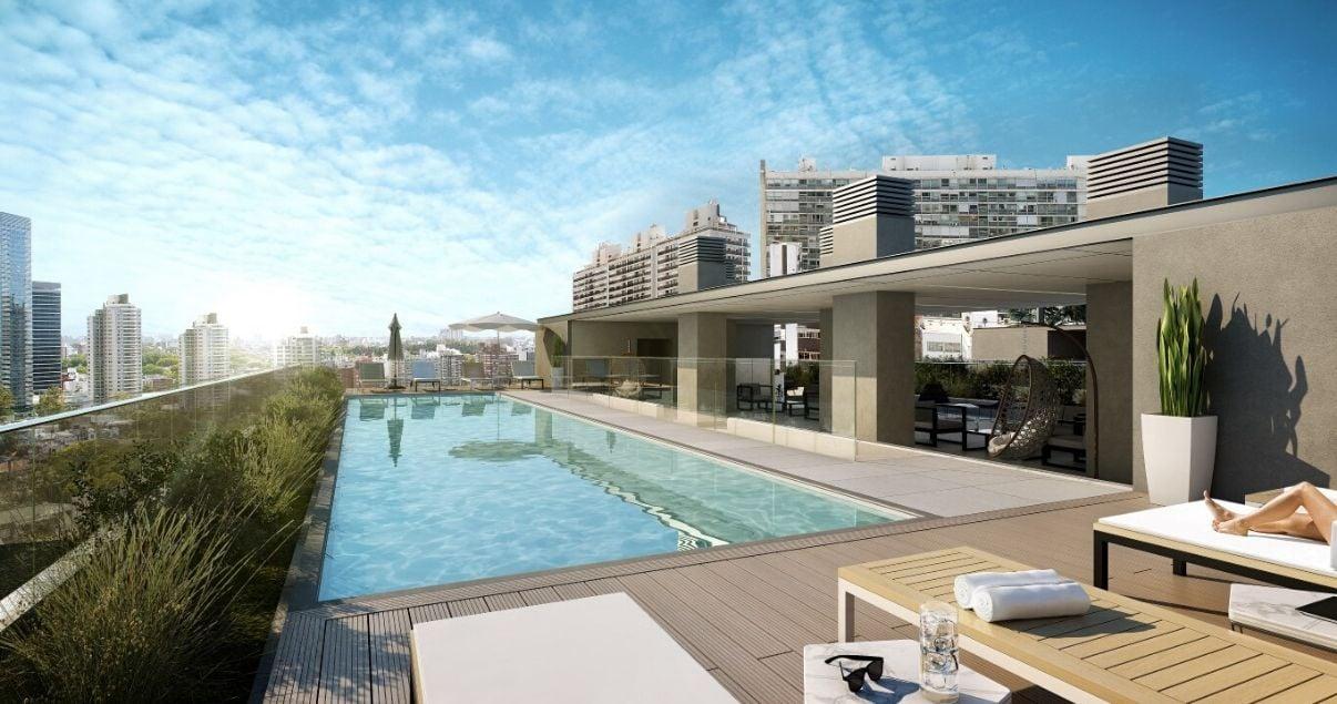 Piscina al aire libre con deck de madera y reposeras en el edificio More Echevarriarza de la desarrolladora inmobiliaria Altius Group