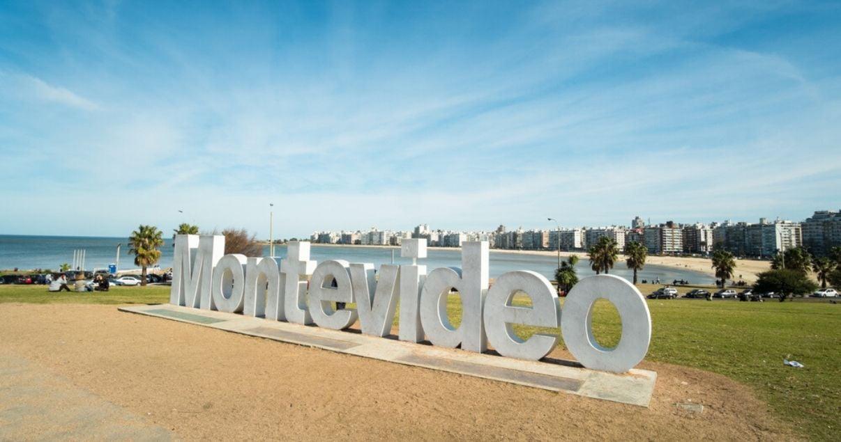 Montevideo escrito en letras gigantes con los barrios del este de fondo y el acceso a la ciudad