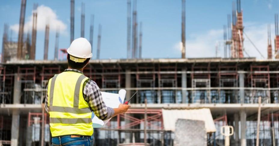 Ingeniero sosteniendo planos del proyecto de apartamento en pozo observando el avance de obra